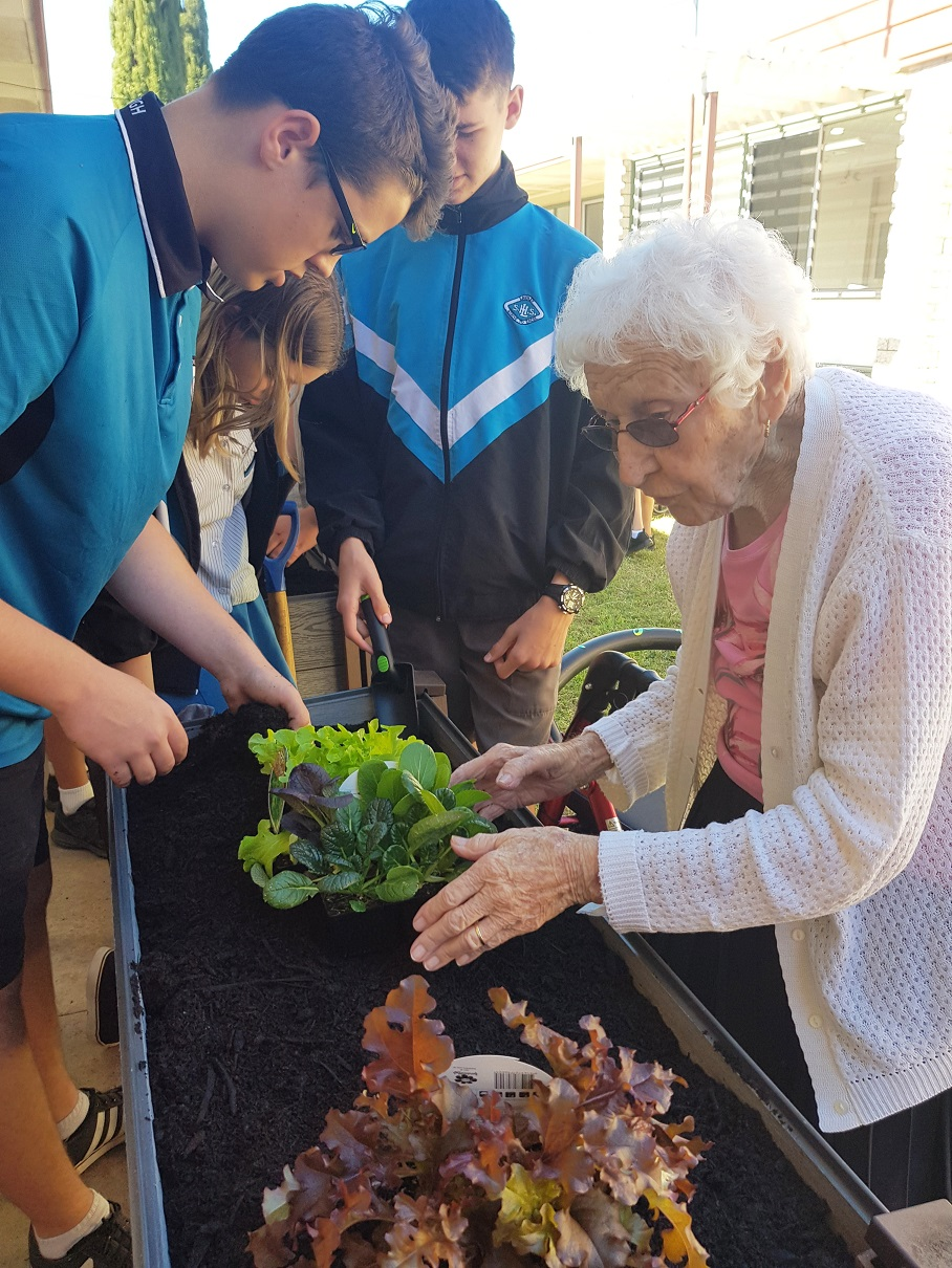 Laidley State High School student Luke Brady and Carinity Karinya Place resident Elsie Pomerenke tend to a garden.