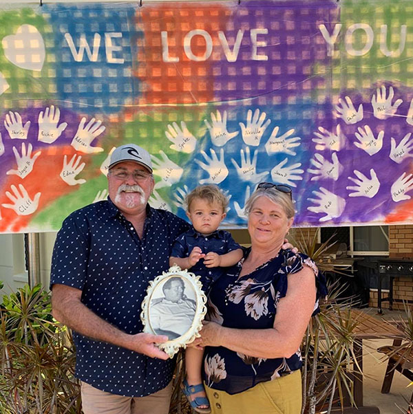Jon Hamilton, Archie Gohdes and Trudi Hamilton hold a photo of Carinity Shalom resident Arthur Hamilton in front of the colourful banner.
