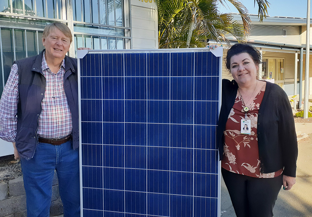 Richard Darvell from Fassifern Sports Club and Samantha Caves with one of the solar panels donated by Carinity Fassifern Community Centre.