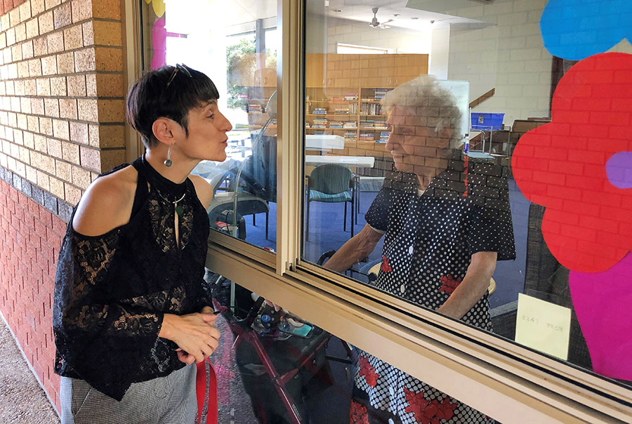 Carinity Wishart Gardens aged care resident Coola Velio and her daughter Avra Velio enjoy a special window chat during coronavirus social isolation restrictions.