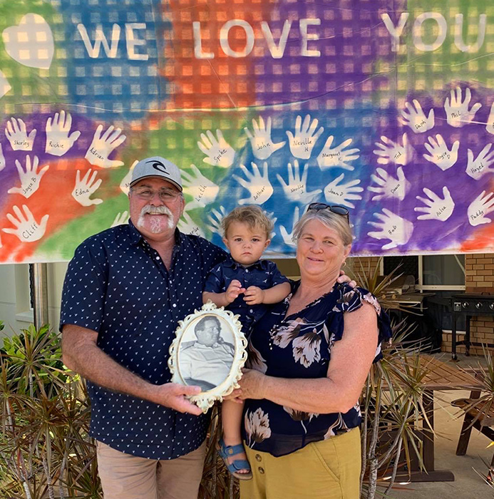 Jon and Trudi Hamilton hold Archie Gohdes and a photo of their relative, resident Arthur Hamilton, in front of a special banner at Carinity Shalom.