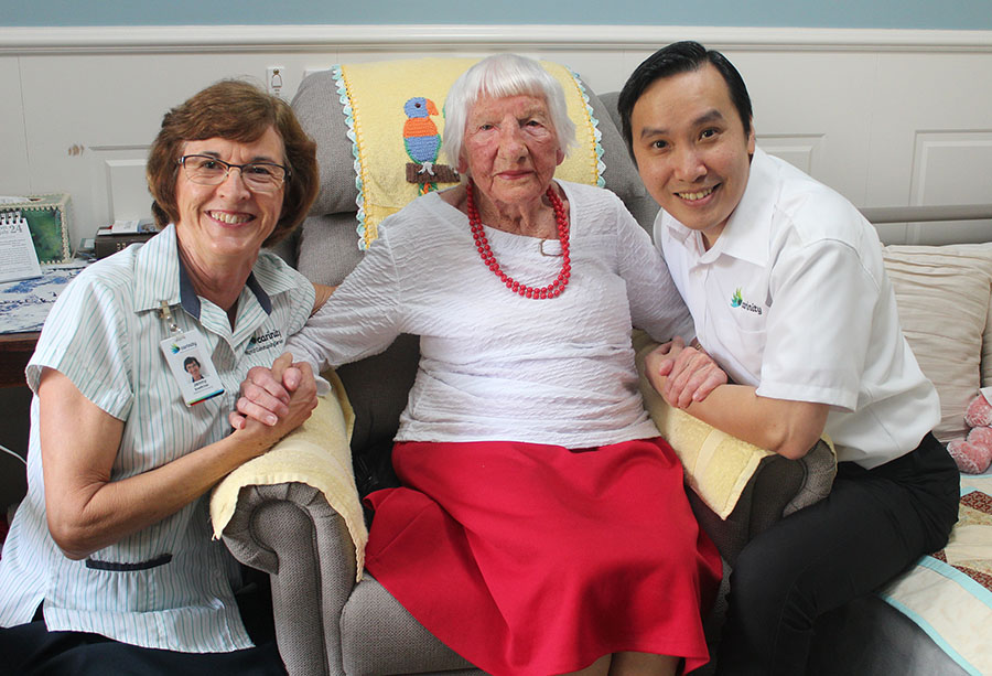 Carinity Wishart Gardens aged care nurses Jenny Boettcher and Derek Or with 102-year-old resident Peggy Muller.