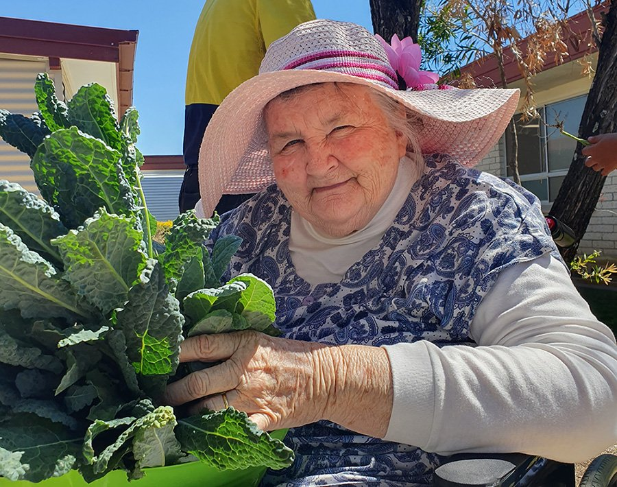 Carinity Karinya Place resident Shirley Sing with vegetables harvested from the aged care community's garden.