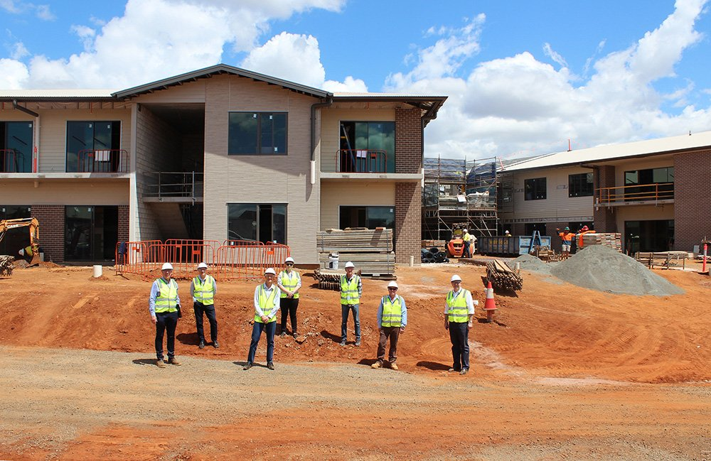 Carinity and Paynters staff inspect construction of the new Carinity aged care building at Highfields.