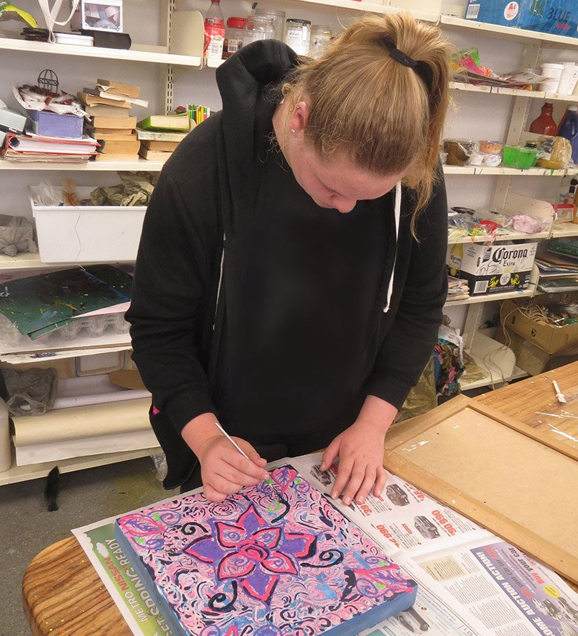 A Carinity Education Southside student doing a painting during art class at the school in Brisbane.