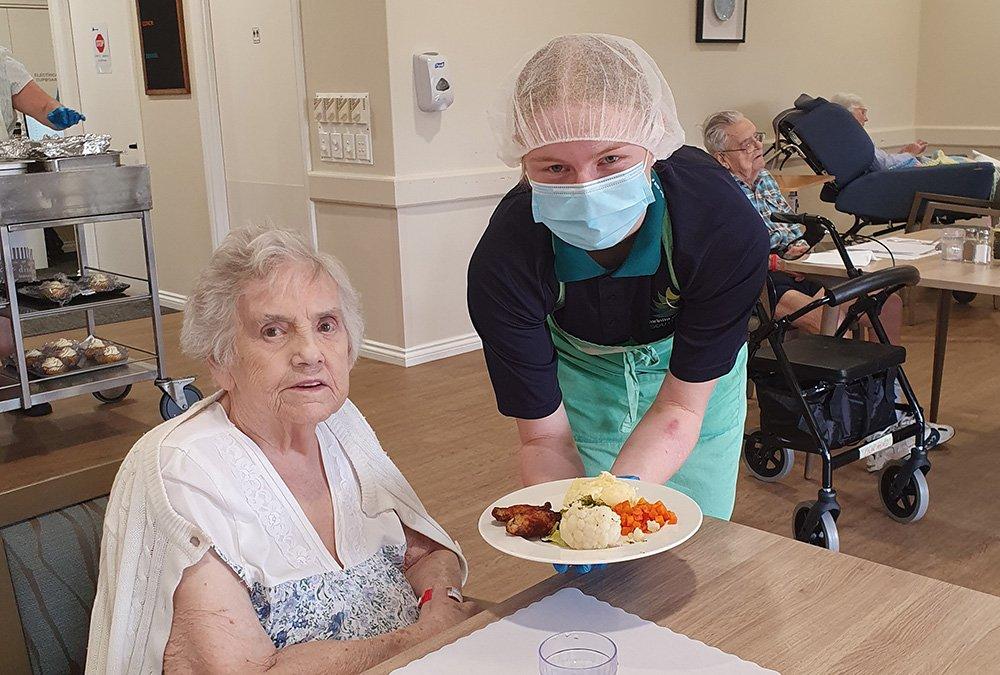 Carinity Education Southside hospitality student Rhiannon serves a Karinya Place resident.