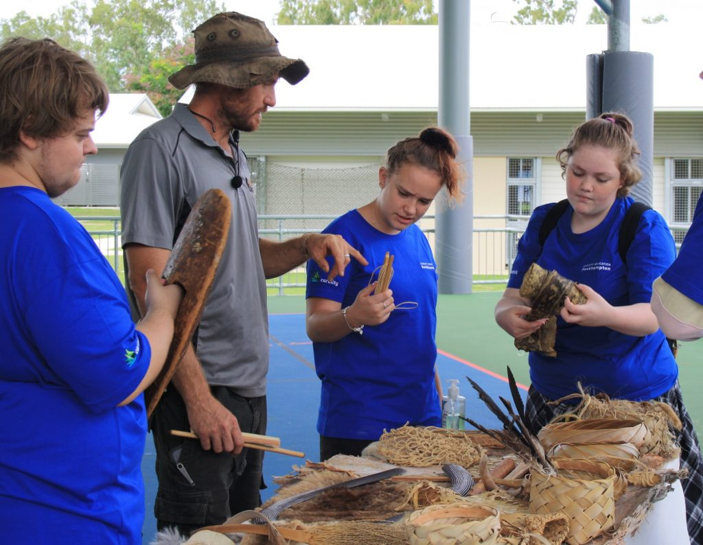 Malachi Conway of Rocky Instincts shows bush tools to Carinity Education Rockhampton students.