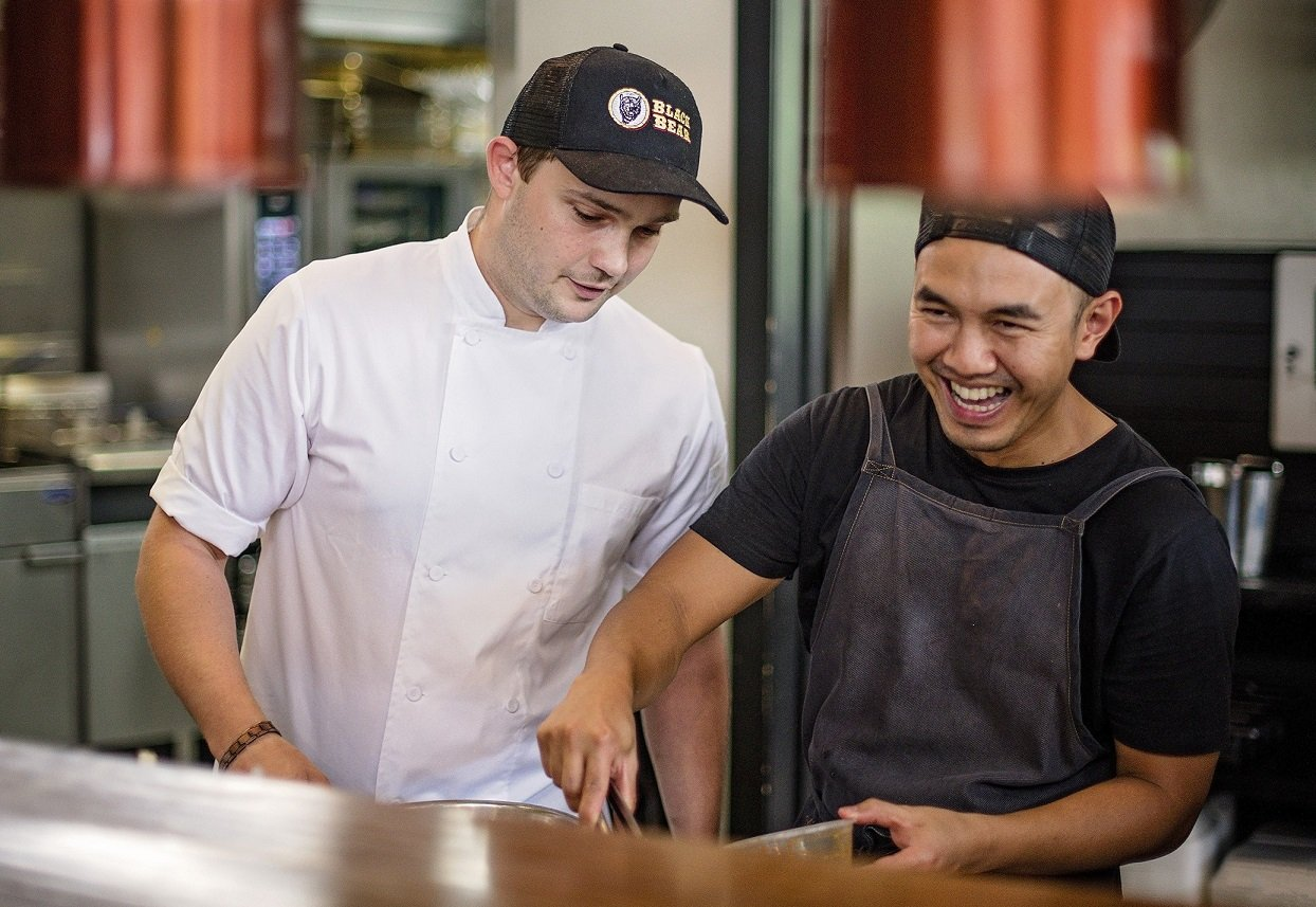 Travis Mares assists Black Bear restaurant workmate Tom Chuamklang to prepare a meal.